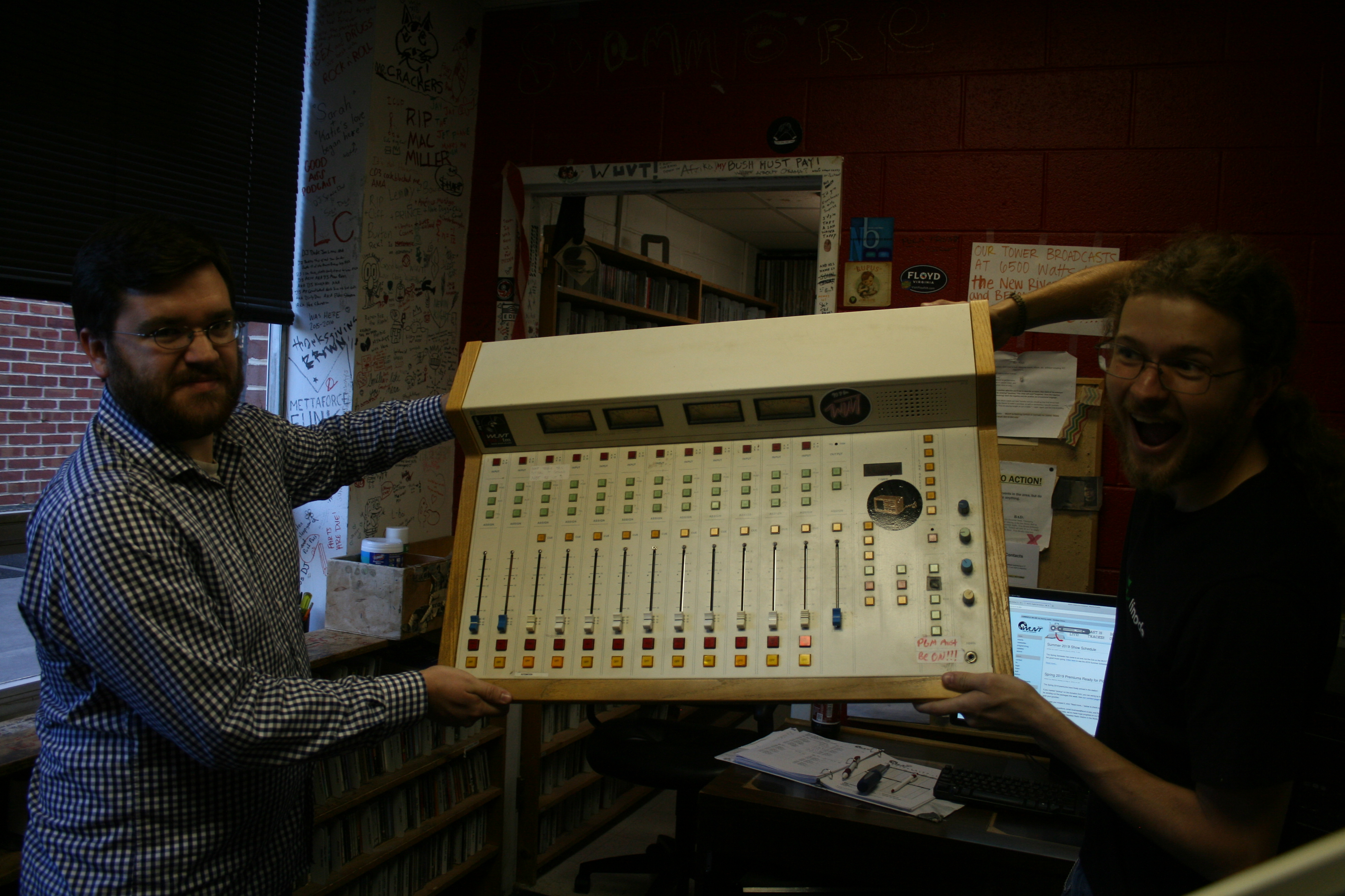a photo of two staff members holding up the old FM board